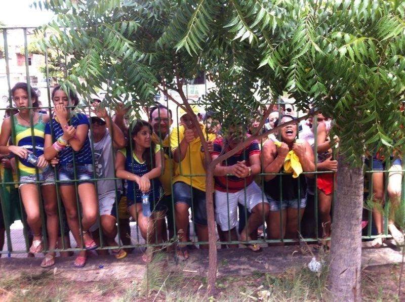Torcedoras se espremem contra a grade do hotel da seleção brasileira