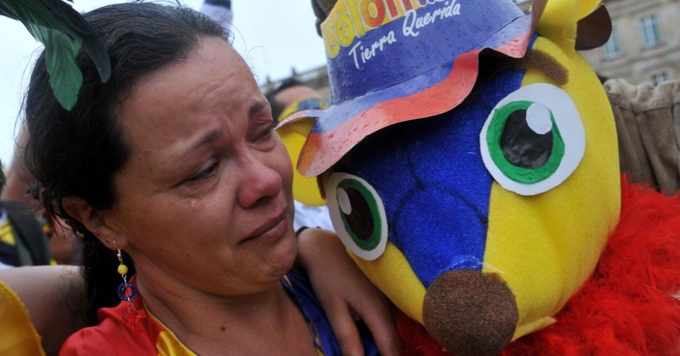 Torcedora colombiana em Bogotá chora eliminação para o Brasil na Copa do Mundo ao lado de boneco do mascote Fuleco
