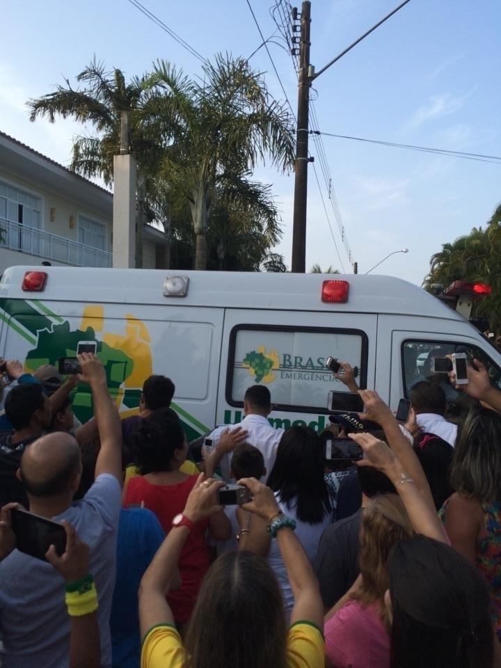 Ambulância com Neymar é cercada por fãs na chegada à residência do atacante, no Guarujá