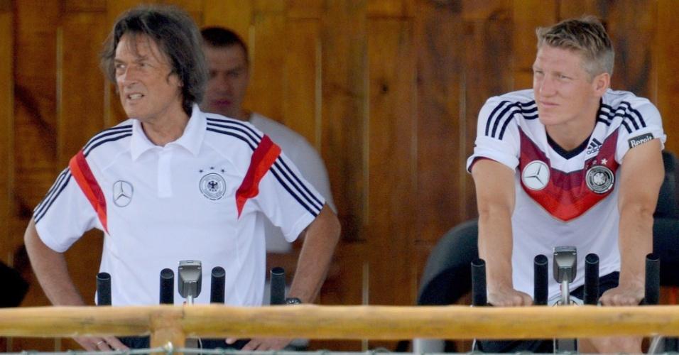 Bastian Schweinsteiger (dir.) e o médico Hans-Wilhelm Mueller-Wohlfahrt fazem exercícios em bicicleta durante treino de bicicleta