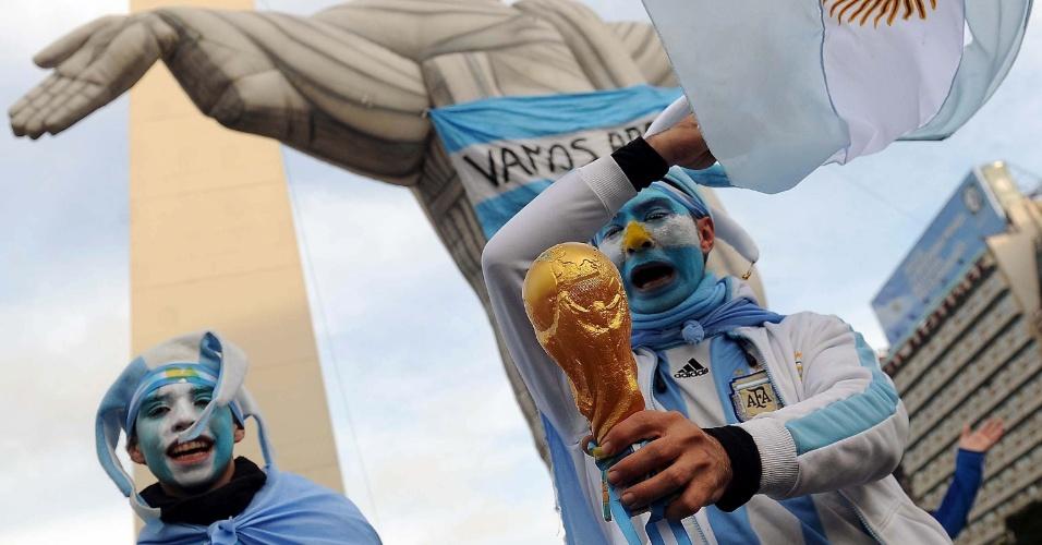 Com a taça na mão e o Cristo atrás, argentinos comemoram a vitória da Argentina sobre a Bélgica na Copa do Mundo
