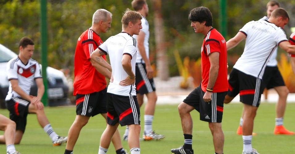 Com o pé na bola, técnico Joachim Löw conversa com Toni Kroos durante treino da Alemanha