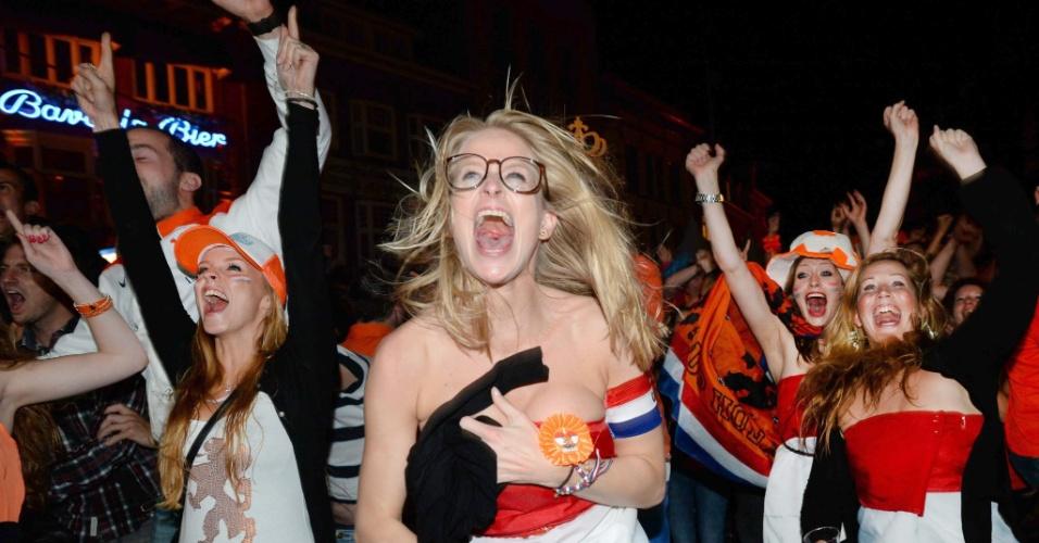 Em Eindhoven, torcedora vibra enrolada à bandeira holandesa após classificação para as semifinais da Copa do Mundo