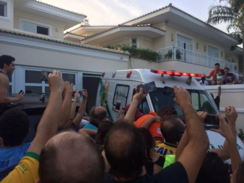 Fãs sobem no muro para acompanhar chegada de Neymar à sua casa no Guarujá