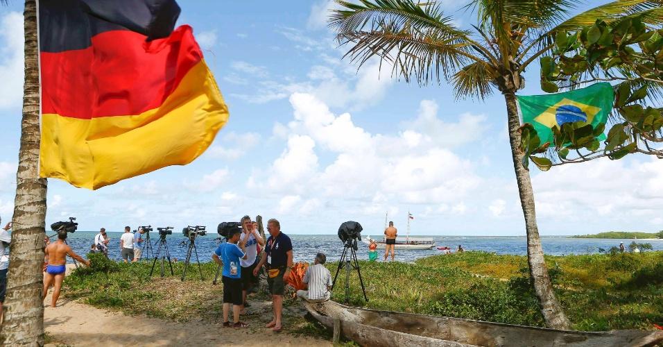 Jornalistas se posicionam em frente ao centro de treinamento da Alemanha, na Bahia. Bandeiras de Alemanha e Brasil podem ser vistas, seleções se enfrentarão pela semifinal da Copa do Mundo