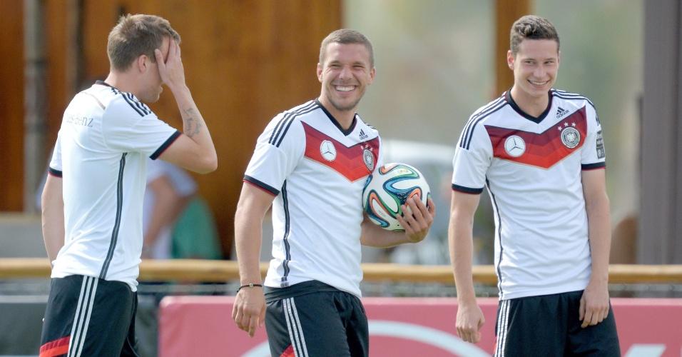 Kevin Grosskreutz, Lukas Podolski e Julian Draxler (esq. para dir.) brincam durante atividade da Alemanha em Santo André, vila próxima a Santa Cruz Cabrália, na Bahia