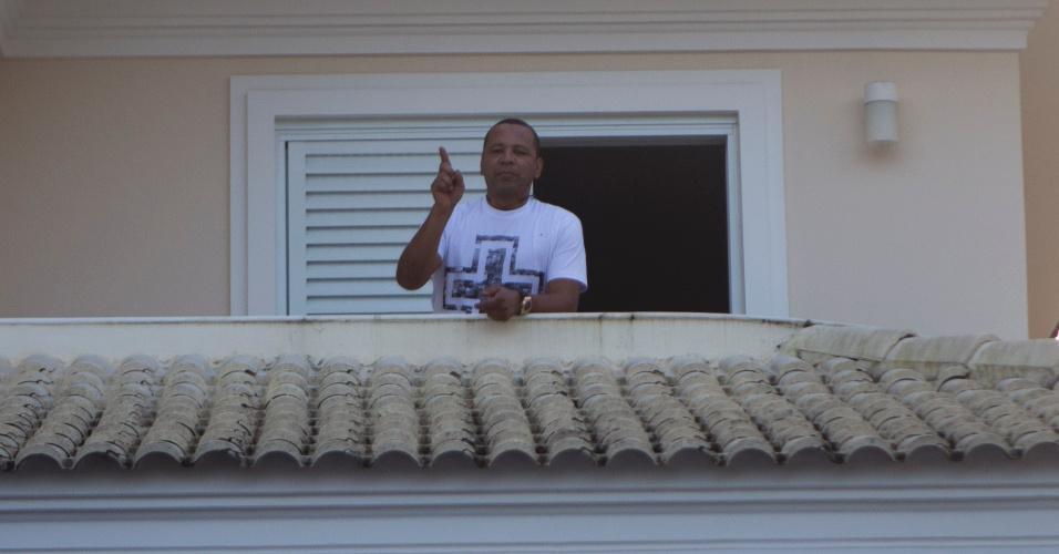 Pai de Neymar sai na janela da casa onde o jogador está, no Guarujá, e acena para os fãs
