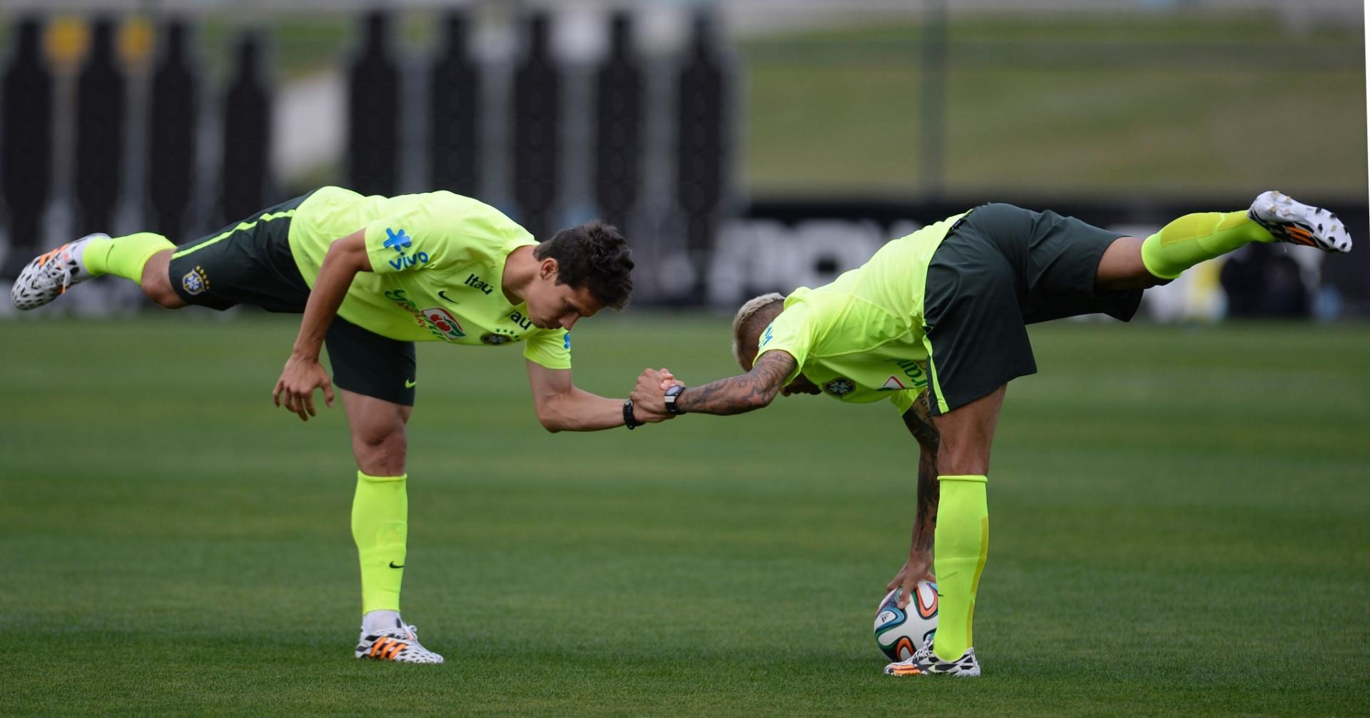 06.jul.2014 - Hernanes e Daniel Alves fazem aquecimento antes de treino da seleção