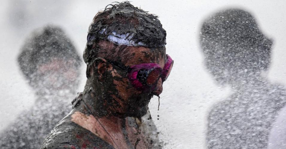 Participante toma banho durante uma pausa entre as competições dos Jogos Olímpicos da Lama
