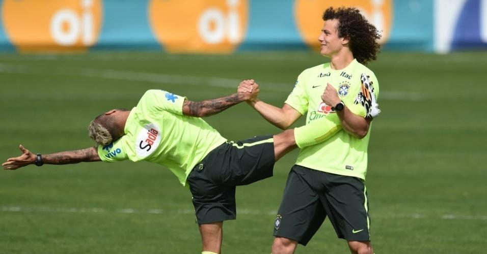 07.jul.2014 - David Luiz ajuda Daniel Alves a fazer alongamento durante o último treino da seleção brasileira na Granja Comary antes da viagem a Belo Horizonte