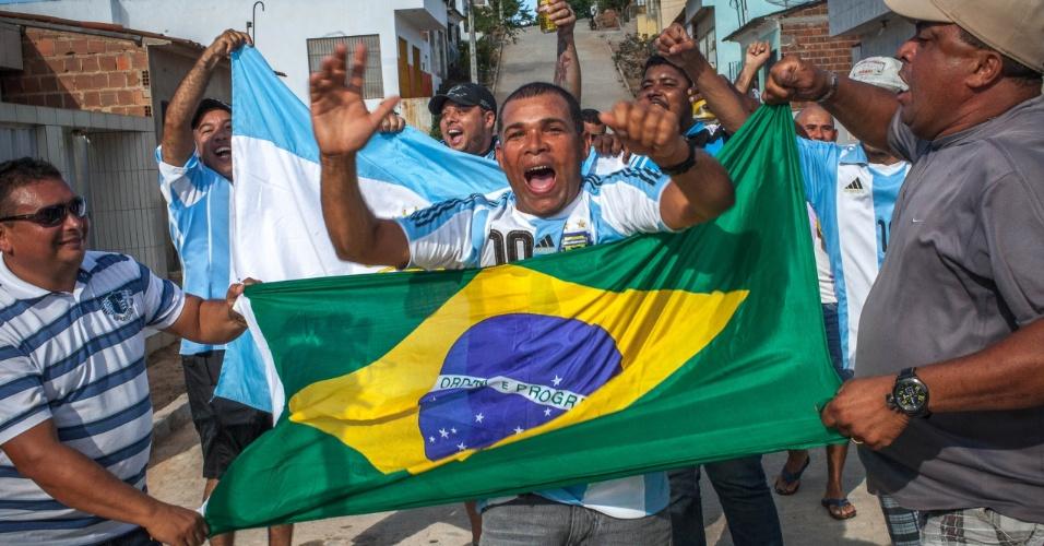Brasileiros comemoram o fim do jogo da Argentina contra a Bélgica na pequena cidade de Buenos Aires