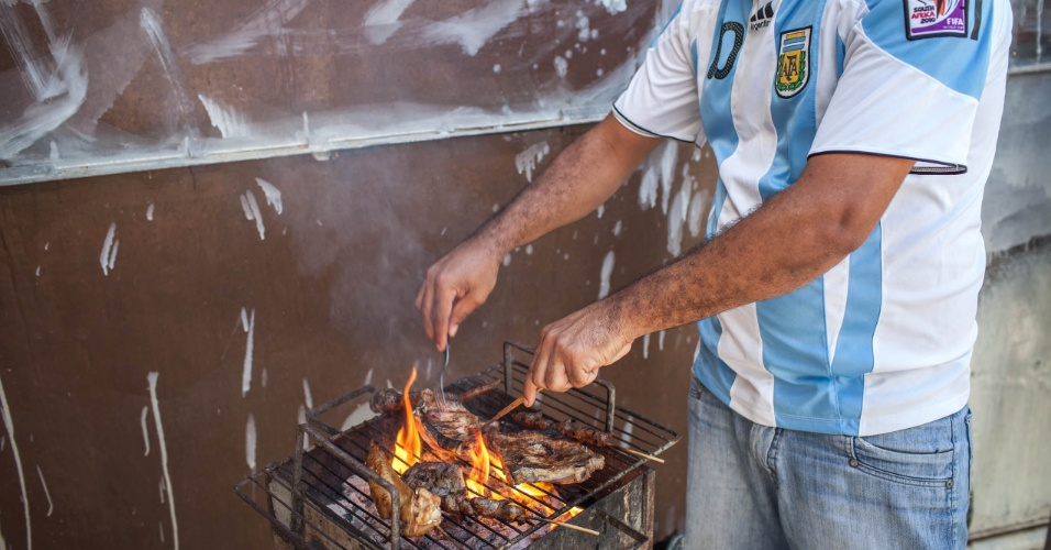 Churrasco brasileiro, com direito a asa e coração de frango e carne de bode, é assado pelo torcedor da Argentina