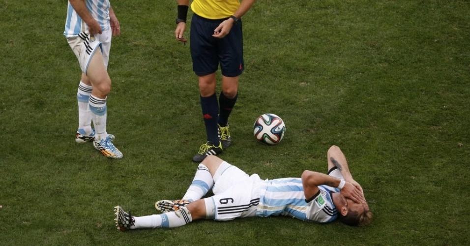 Messi mostra coxa enquanto Biglia desaba no chão depois de sofrer falta nas quartas de final contra a Bélgica, em Brasília