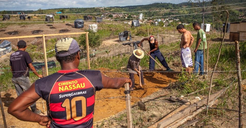 Moradores do assentamento do MST trabalham para levantar um novo barraco, minutos antes da partida da seleção brasileira contra a Colômbia
