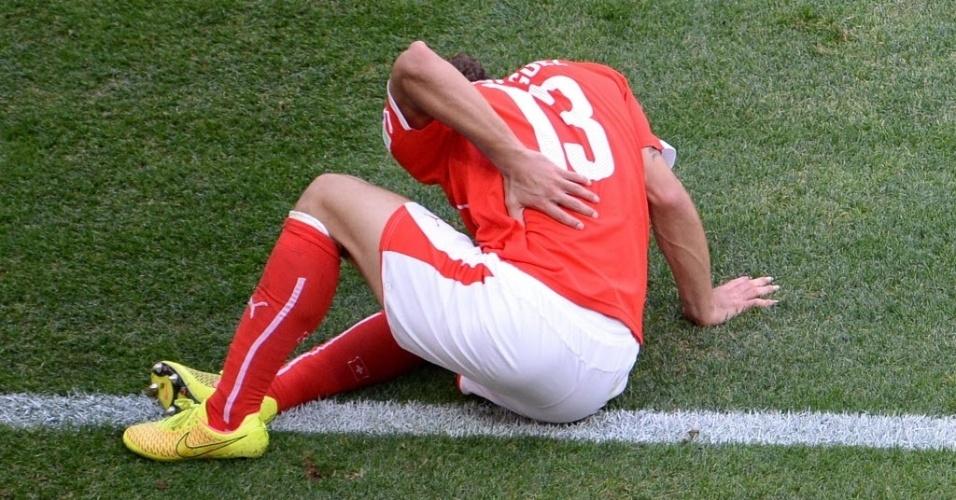 O zagueiro da Suíça, Ricardo Rodríguez, tenta aliviar a pancada nas costas durante o jogo contra Equador, no estádio Mané Garrincha