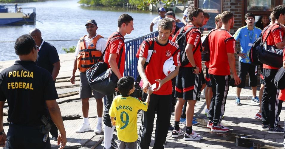 Thomas Müller dá autógrafo para criança com a camisa do Brasil, rival da Alemanha nas semifinais da Copa do Mundo. Seleção tricampeã mundial deixa Santa Cruz Cabrália, na Bahia, com destino a Belo Horizonte