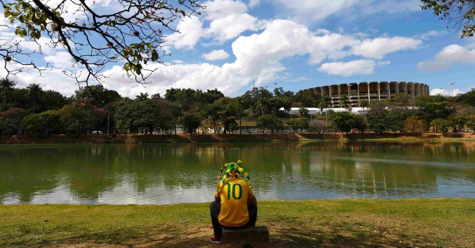 Com o Mineirão ao fundo, torcedor aguarda o início da primeira semifinal da Copa, entre Brasil e Alemanha