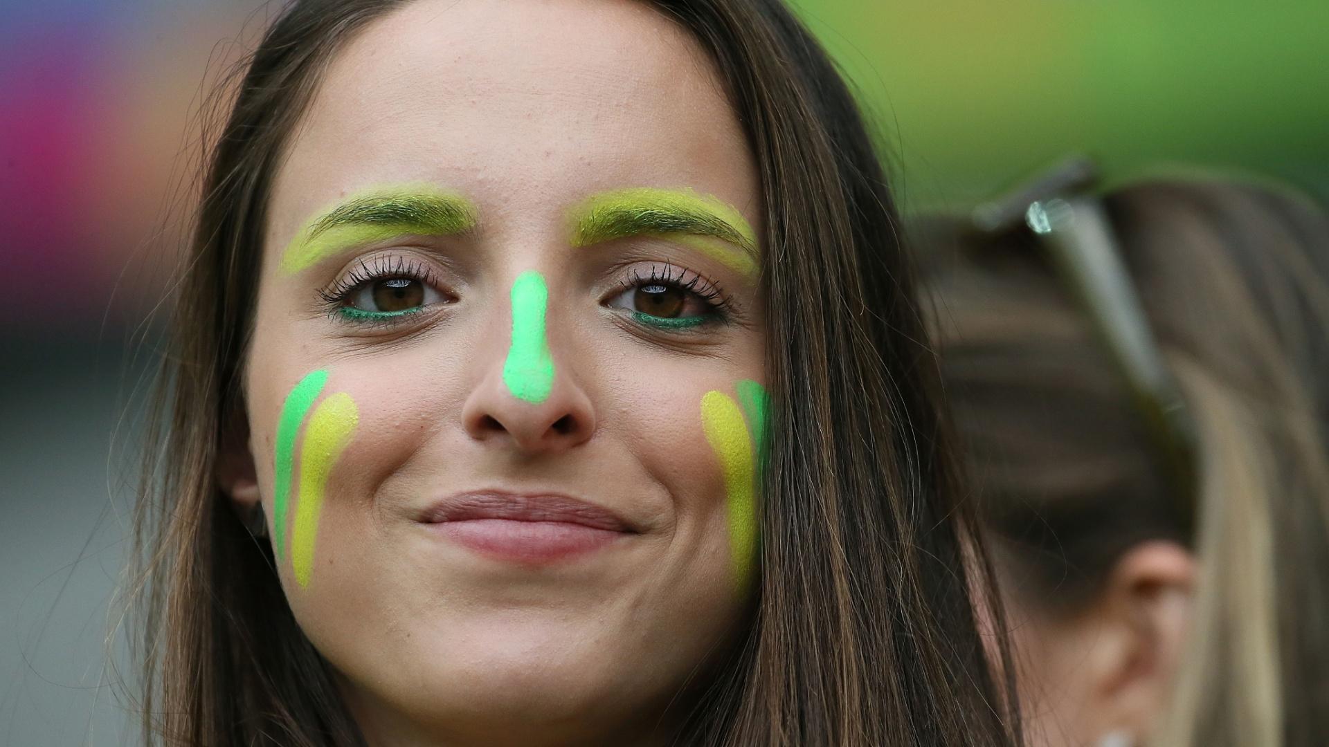 Com o rosto pintado, torcedora espera o início da partida entre Brasil e Alemanha, no Minerão