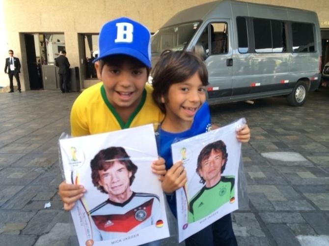 """Em frente ao hotel no qual está hospedada a seleção brasileira em Belo Horizonte, torcedores seguram """"figurinhas de Mick Jagger"""" vestido com uniforme da Alemanha"""
