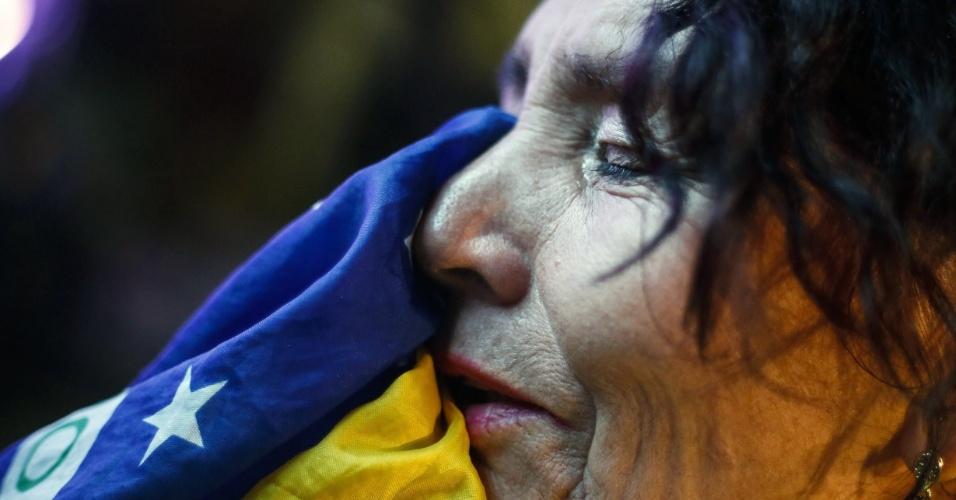 Mulher chora na bandeira brasileira por eliminação para a Alemanha