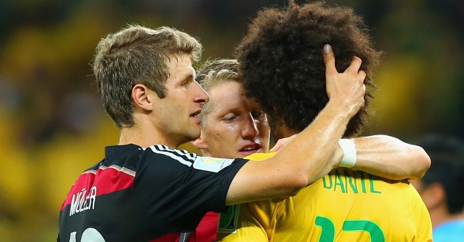 Müller e Schweinsteiger consolam o brasileiro Dante, companheiro de Bayern de Munique, após a vitória alemã por 7 a 1, no Mineirão