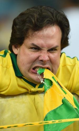 08. jul. 2014 - O torcedor não gostou nada da goleada sofrida para a Alemanha no Mineirão e mordeu a bandeira do Brasil