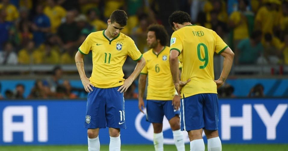 Oscar e Fred mostram abatimento após sofrer mais um gol para a Alemanha, no primeiro tempo no Mineirão