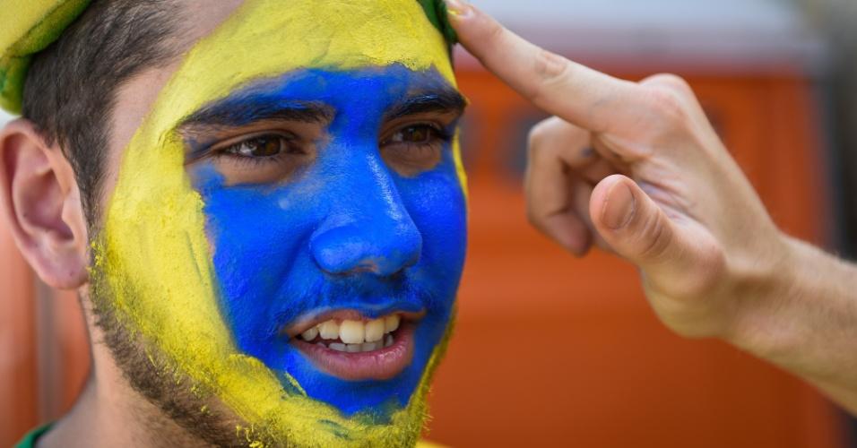 Torcedor tem o rosto pintado com a bandeira do Brasil antes do jogo contra a Alemanha, pela semifinal da Copa do Mundo
