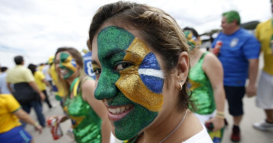 Torcedora pinta o rosto com a bandeira do Brasil do lado de fora do Mineirão