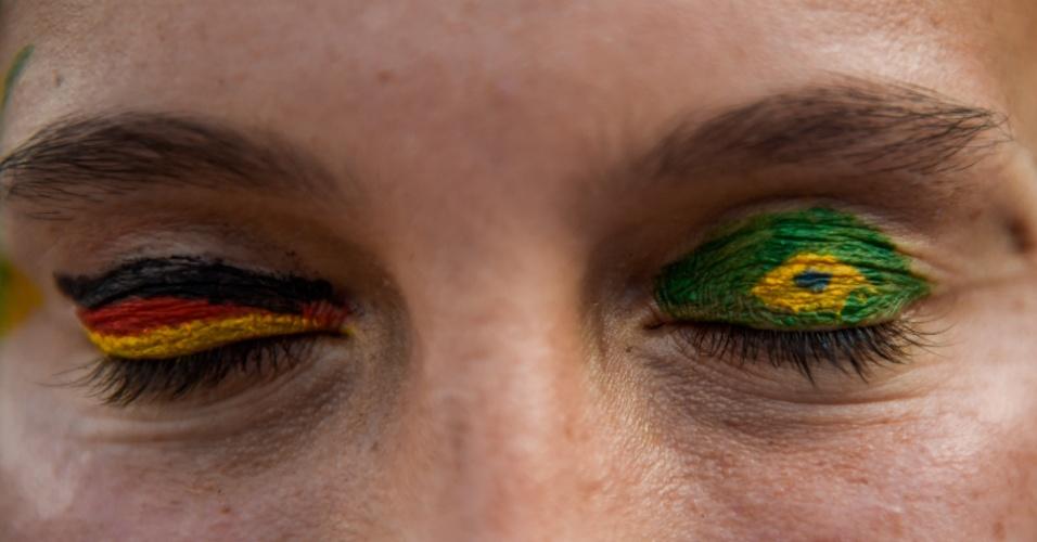 Um olho alemão, outro brasileiro. Torcedor pinta as bandeiras de Alemanha e do Brasil antes do jogo no Mineirão