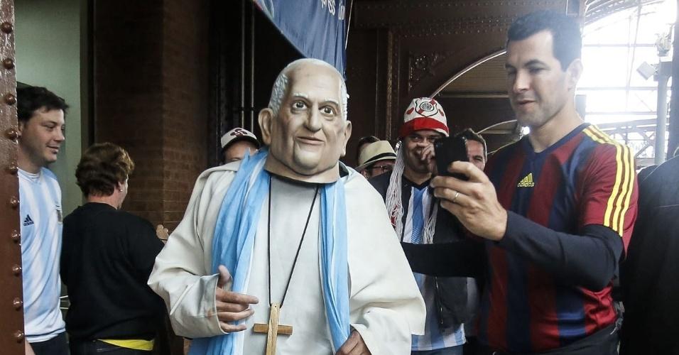 Torcedor argentino fantasiado de Papa Francisco caminha por estação de metrô, em São Paulo