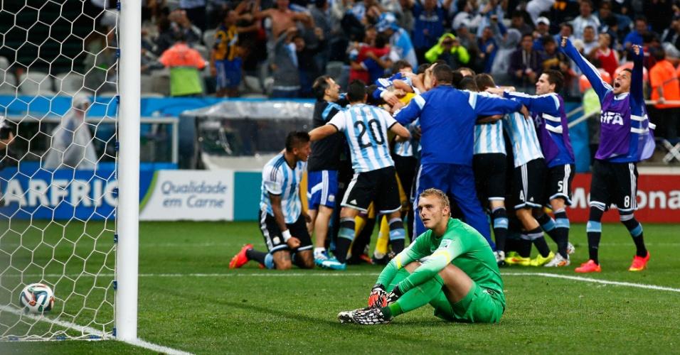 Argentinos comemoram enquanto o goleiro Jasper Cillessen lamenta no gramado após a derrota da Holanda