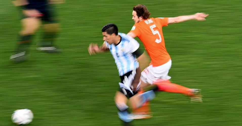 Enzo Perez tenta escapar da marcação de Blind na semifinal entre Argentina e Holanda