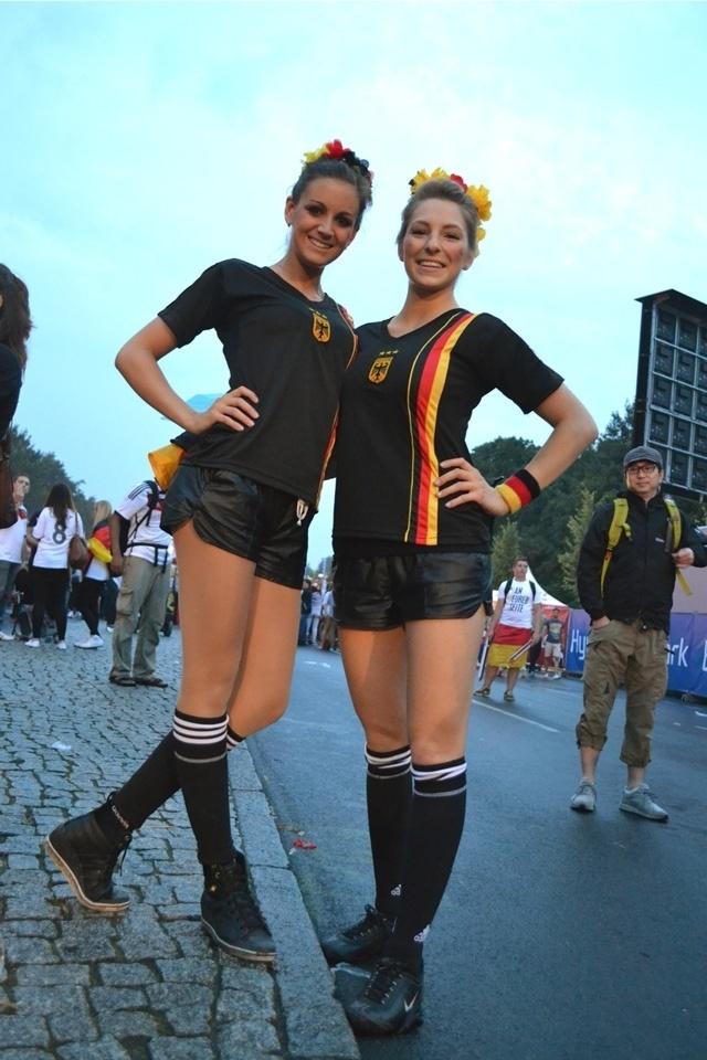Torcedoras alemãs viram juízas para assistir à partida no Portão de Brandemburgo. O look foi aprovado pelo torcedor à direita