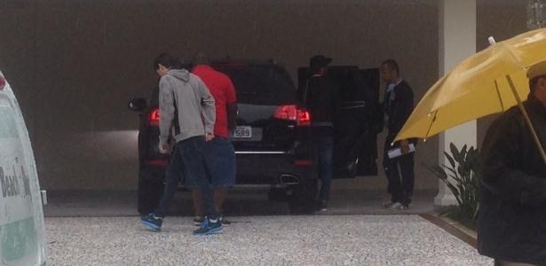 De boné, ao lado do pai, Neymar entra no carro caminhando normalmente nesta quinta-feira, no Guarujá