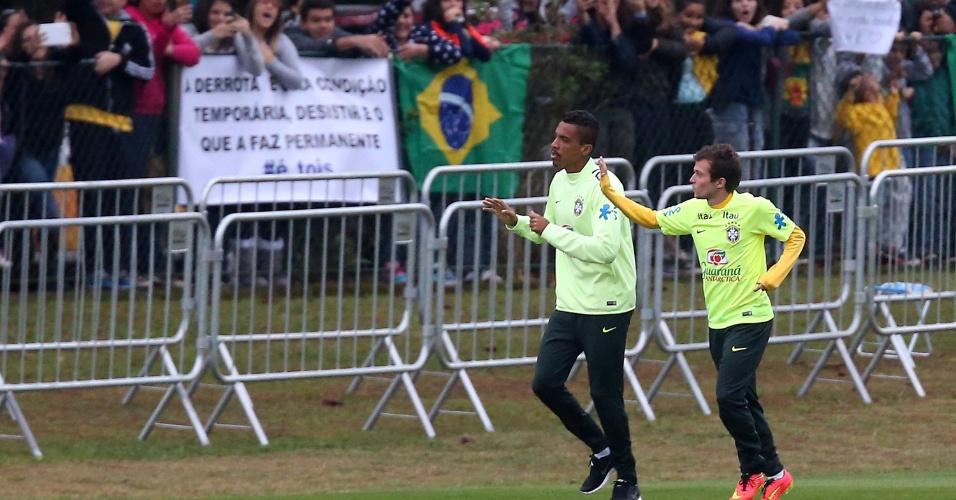 Luiz Gustavo e Bernard acenam para torcida durante treinamento realizado na Granja Comary