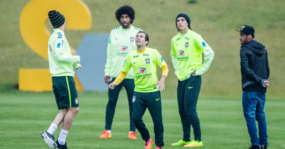Neymar observa companheiros de seleção brincando com a bola no gramado da Granja Comary