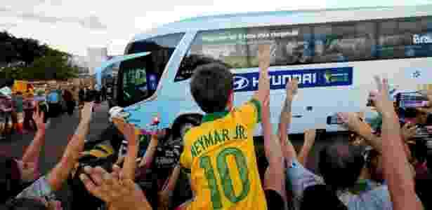Menino com camisa de Neymar acena para ônibus da seleção brasileira durante chegada da equipe a hotel em Brasília - Pedro Ladeira/Folhapress