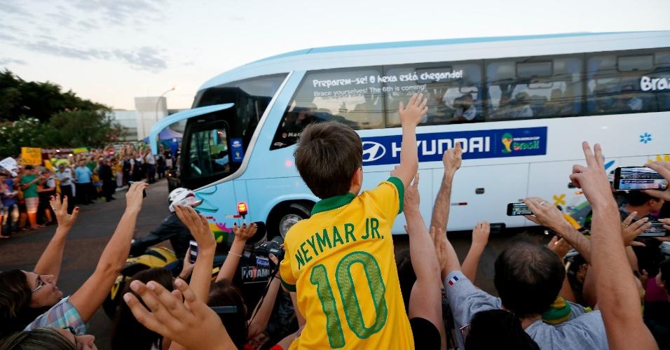 Menino com camisa de Neymar acena para ônibus da seleção brasileira durante chegada da equipe a hotel em Brasília