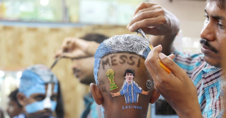 Fã da Argentina faz corte especial de cabelo com o desenho de Messi em Calcutá, na Índia, um dia antes da final da Copa, contra a Alemanha