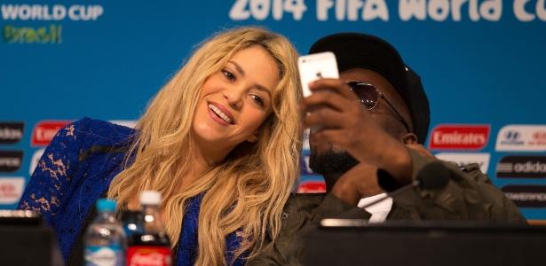 Shakira tira selfie ao lado do rapper Wyclef Jean durante entrevista coletiva sobre a cerimônia de encerramento da Copa do Mundo no Brasil