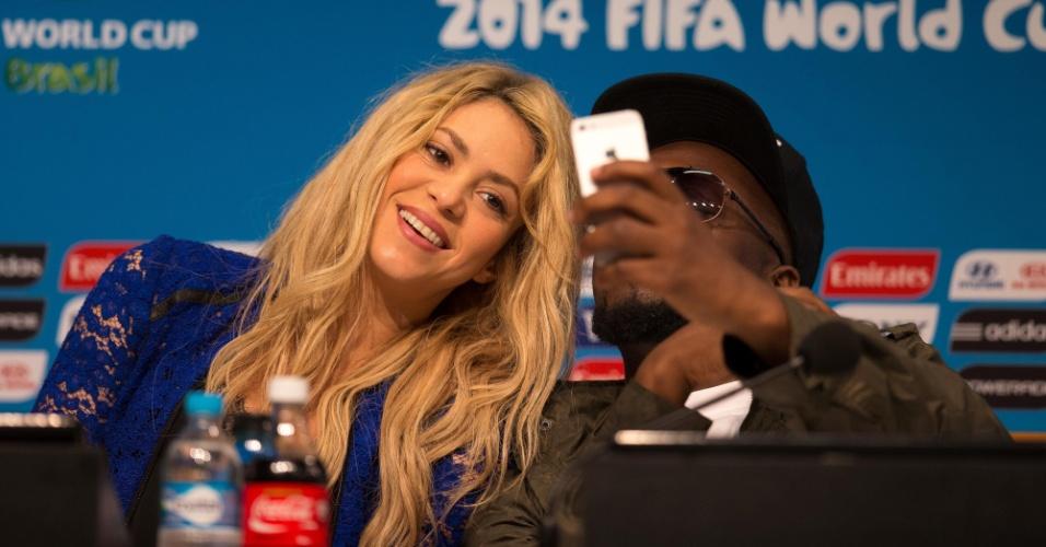 Shakira tira selfie ao laod do rapper Wyclef Jean durante entrevista coletiva sobre a cerimônia de encerramento da Copa do Mundo no Brasil