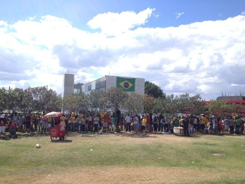 Torcedores ficam próximos à grade do hotel em que a seleção brasileira está concentrada aguardando a saída do time com destino ao estádio Nacional de Brasília