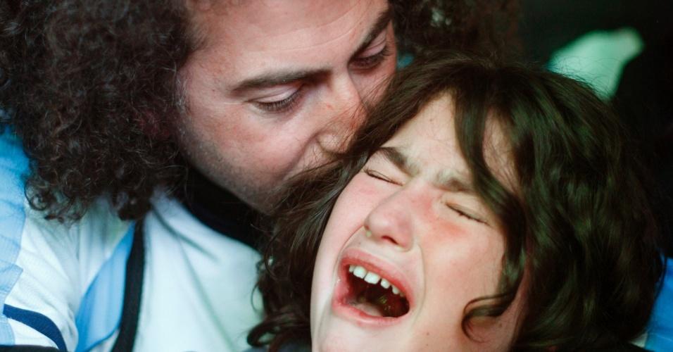 Em Buenos Aires, pai consola filho que se desespera após derrota da seleção argentina na final da Copa do Mundo