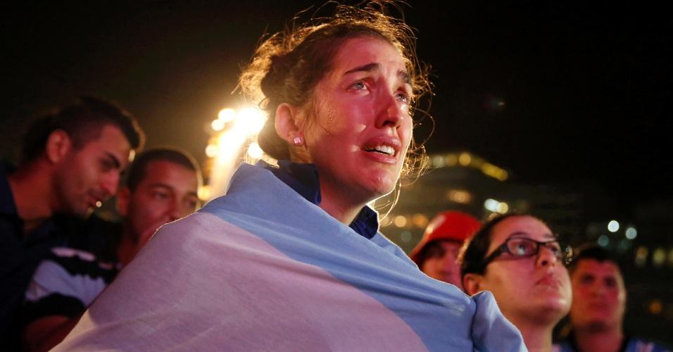 Enrolada na bandeira argentina, torcedora chora na praia de Copacabana perda do título para a Alemanha