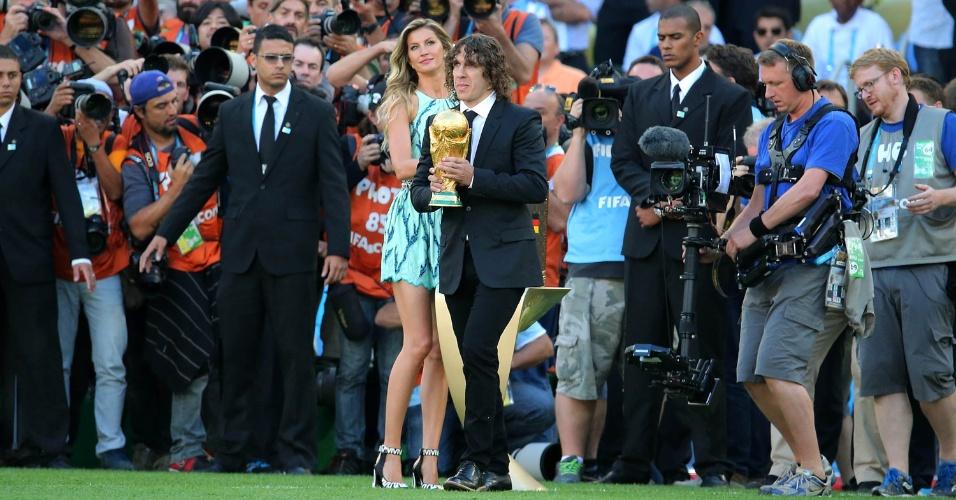 Gisele Bündchen e o espanhol Carles Puyol entram no gramado do Maracanã levando a Taça da Copa do Mundo