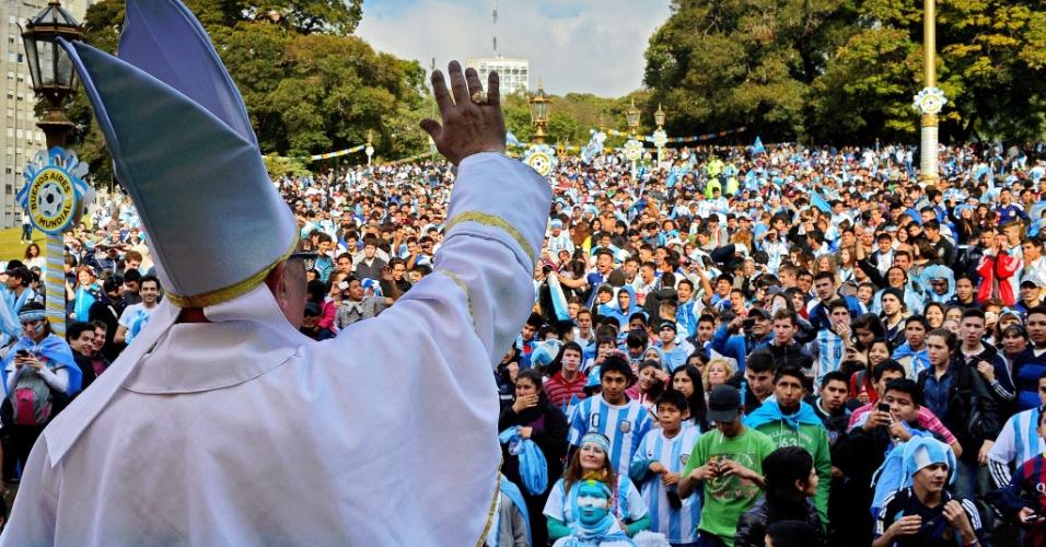 Homem fantasiado de papa acena para os torcedores argentinos na praça San Martin, em Buenos Aires, antes da final da Copa do Mundo contra a Alemanha