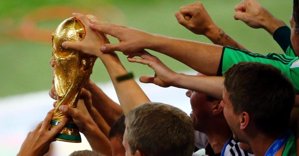 Jogadores da Alemanha tentam tocar a taça após a vitória sobre a Argentina na final da Copa