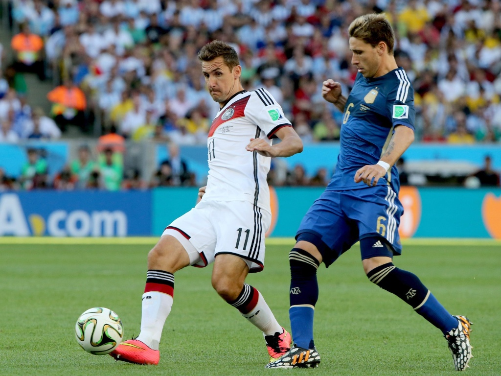 Klose toca a bola marcado de perto pelo argentino Biglia