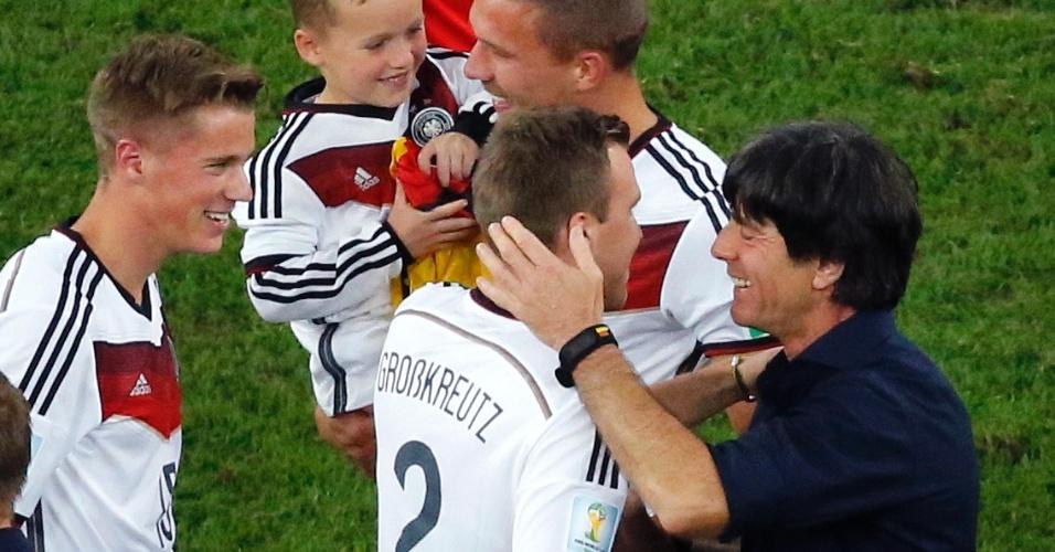 Podolski leva o filho no campo para comemorar o título da Alemanha, junto com o técnico Joachim Löw e Kevin Grosskreutz